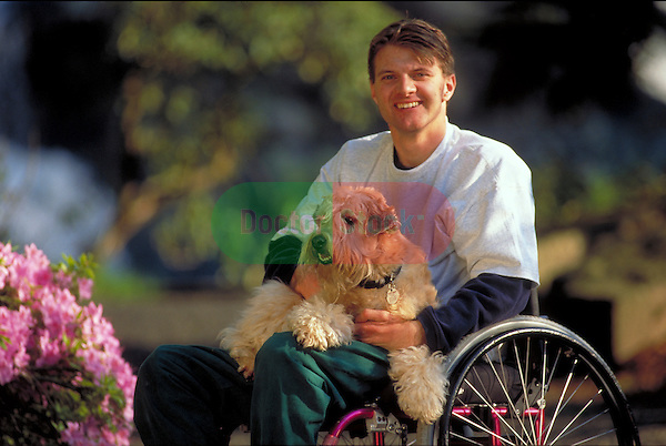 man in wheelchair holding pet dog