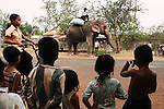 CAMBODIA  -  APRIL 5, 2005:  People stop to watch an elephant in a village between Phnom Penh and Kampot on April 5th, 2005 in Cambodia.  (PHOTOGRAPH BY MICHAEL NAGLE)