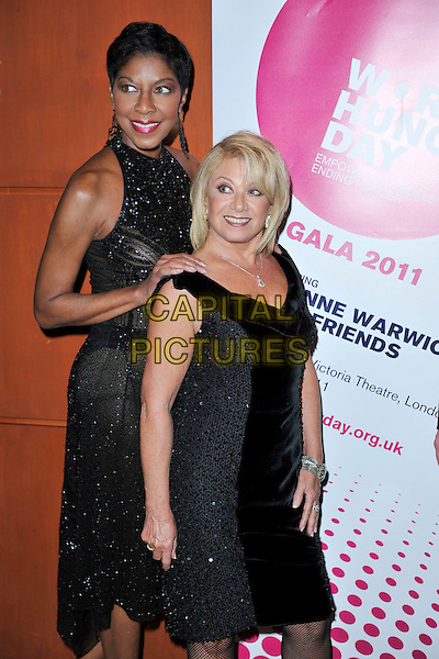 NATALIE COLE, ELAINE PAIGE<br /> attends The Hunger Project Concert after party as part of World Hunger Day 2011 at the Park Plaza Hotel in London, England, UK, January 9th, 2011.<br /> half length black sleeveless dress velvet tall short beaded sparkly hand on shoulder <br /> CAP/MAR<br /> &not;&copy; Martin Harris/Capital Pictures
