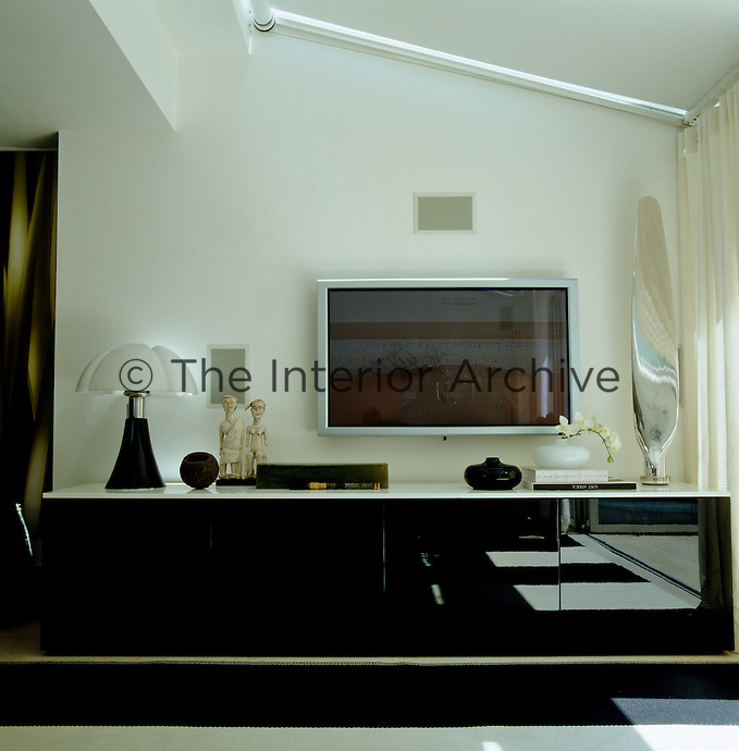 A sleek modern sideboard and large plasma screen in the family room