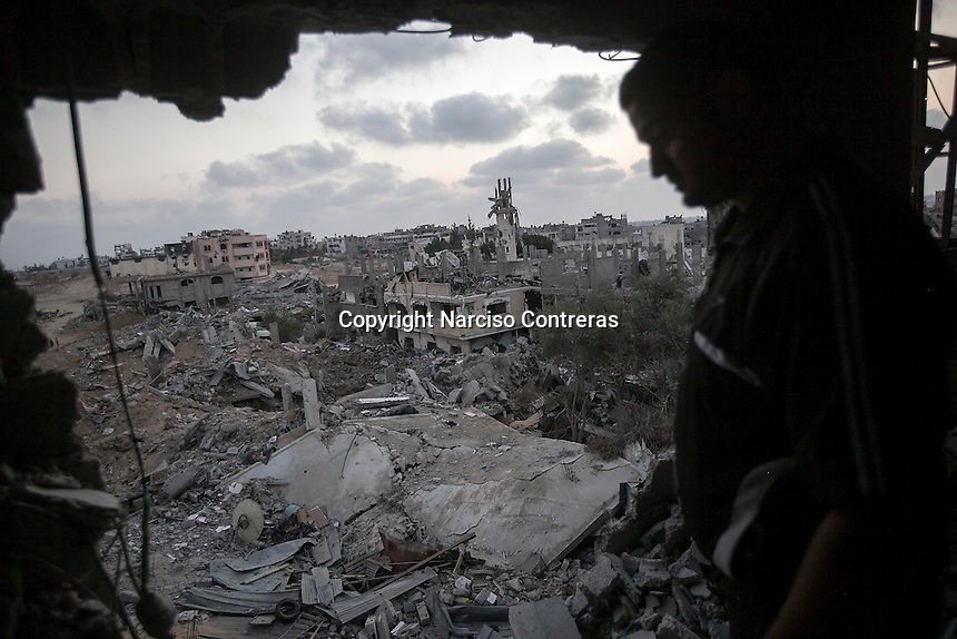 "In this Sunday, Aug. 17, 2014 photo, a Palestinian man looks for his belongings among the rubble of his house destroyed by israeli airstrikes and artillery shelling during the ""Protective Edge"" military operation in Shuyaja neighborhood in Gaza City. After a five days truce was declared on 13th August between Hamas and Israel, civilian population went back to what remains from their houses and goods in Gaza Strip. (Photo/Narciso Contreras)"