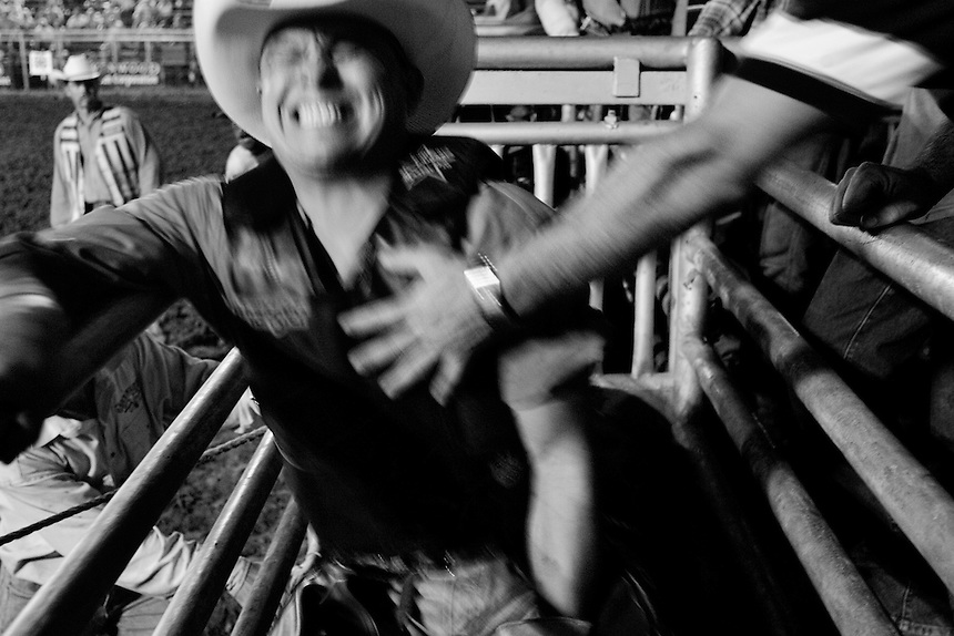 David Gonzales of San Antonio receives a helping hand as he gets rattled in the chute at the rodeo in Wimberley, Texas. September 4, 2007.