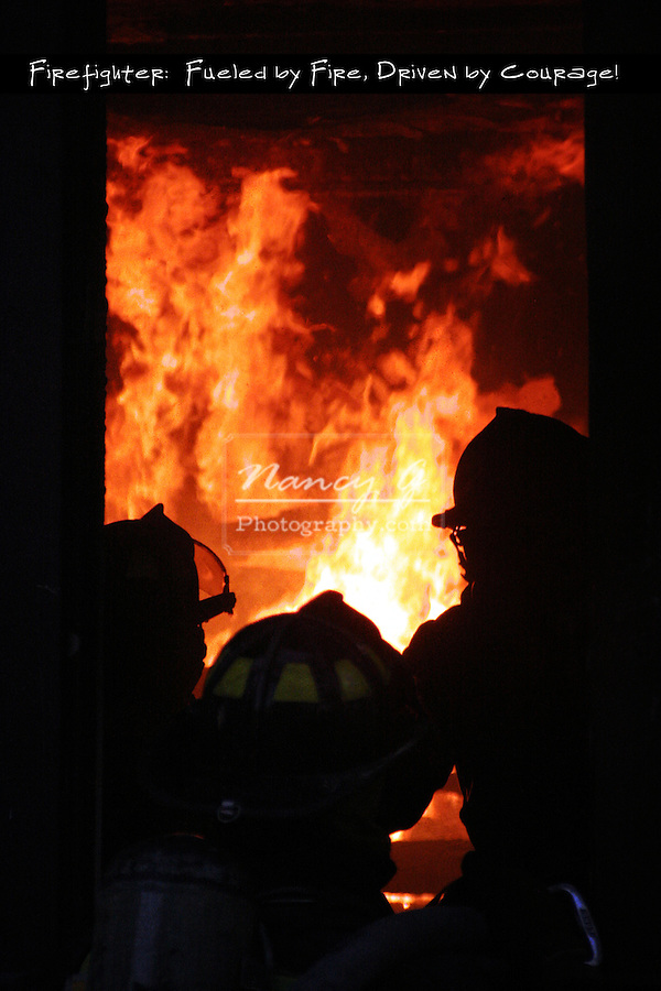 Three firefighters looking in on a room of a house on fire before putting out the flames