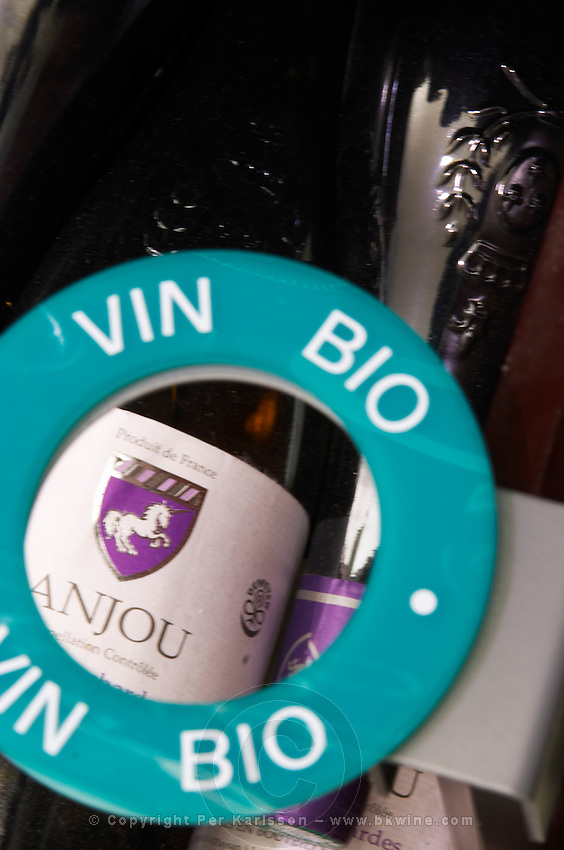 A round sign indicating Vin Bio, biodynamic wine organic organically grown wine with a bottle of wine from Anjou, Loire Valley. The Lavinia wine shop in Paris. Probably the biggest wine shop in Paris, with its special temperature controlled section for wines that are fragile and must be stored at cool low temperature.