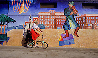 woman on foldable bycycle in front of wall paintings in Venice, Los Angeles, California, USA