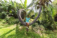 A woman sits on an unusual-looking curly palm tree in Kealakekua, Big Island.