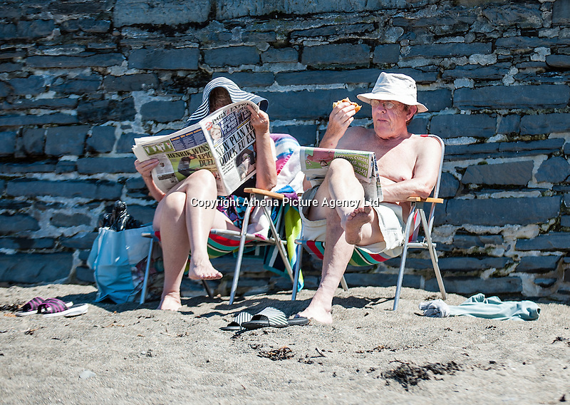 UK Weather: Aberystwyth, Ceredigion, West Wales Monday 18th July 2016. A couple lounge on the beach reading newspapers. The RNLI are out in force both making sure people are safe and raising awareness of the work they do.  Although it is overcast the sun is breaking through and the temperatures are expected to hit the low 20C with the mini heat wave expected to continue tomorrow reaching 30