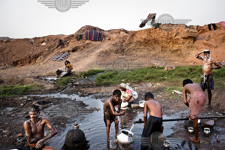 After a day of tiring labour, miners wash themselves clean of grime and coal dust. They work for about 10 hours a day, loading coal trucks in the BCCL coal mines, for which they receive 150 Indian Rupees (3.5USD).