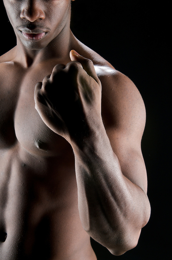Close up of hands of a bodybuilder in deep shadow to accentuate drama.