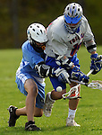 East Catholic 4, Jake Gonzalez, and Tolland 19, Kevin Kilguss, battle for a loose ball, during the first half of their game at Tolland High School, Tuesday, May 10, 2011. (Jim Michaud/Journal Inquirer)