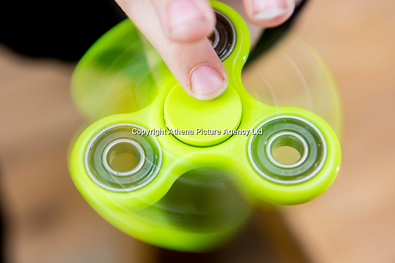 A young boy uses a bright green fidget spinner