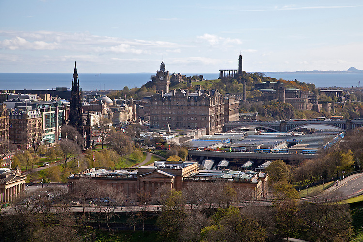 View of downtown Edinburgh, including the Scott Monument on the left, Calton Hill in the background, and Edinburgh Train Station in middle right, and the Scottish National Gallery in the foreground, in Scotland, United Kingdom