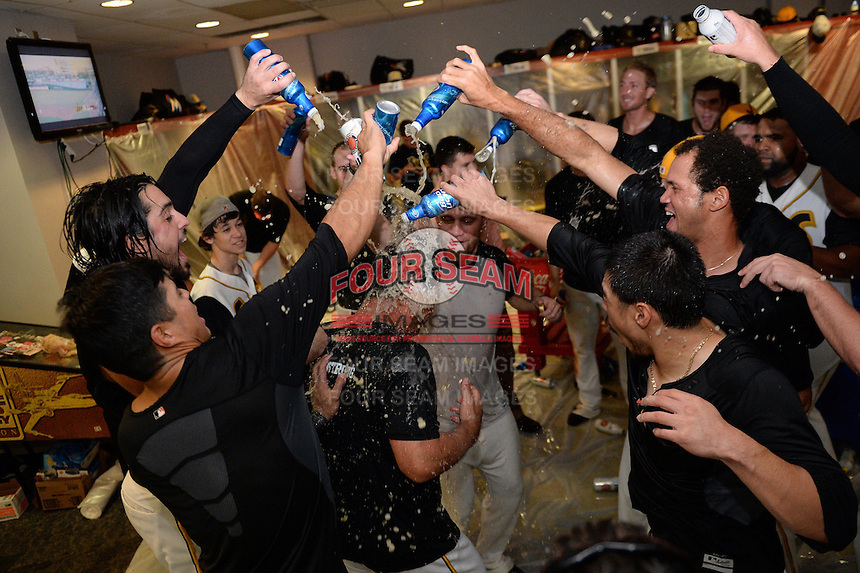 Jacksonville Suns players douse coach Rich Arena (14) in the locker room after game three of the Southern League Championship Series against the Chattanooga Lookouts on September 12, 2014 at Bragan Field in Jacksonville, Florida.  Jacksonville defeated Chattanooga 6-1 to sweep three games to none.  (Mike Janes/Four Seam Images)