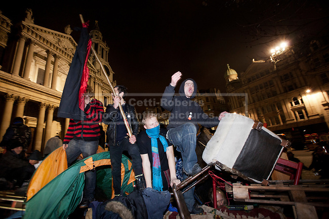 28/02/2012. LONDON, UK. Occupy London protesters stands on top of a barricade of pallets and shelving as they attempt to avoid police and bailiffs. After being camped outside St Paul's Cathedral in London for four months anti-capitalist Occupy London demonstrators were tonight evicted by police and bailiffs who moved in shortly after midnight. Photo credit: Matt Cetti-Roberts