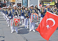 Young girls and boys walking along the parade and carrying the country flag and Ataturk pictures and singing the national anthem during the celebration of Turkey's national day at Istiklal Street, Taksim.