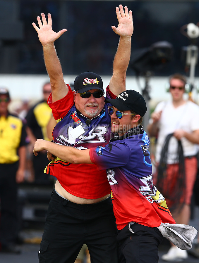 Jun. 2, 2013; Englishtown, NJ, USA: NHRA pro stock motorcycle team owner George Bryce (left) celebrates with a crew member after rider Michael Ray wins the Summer Nationals at Raceway Park. Mandatory Credit: Mark J. Rebilas-
