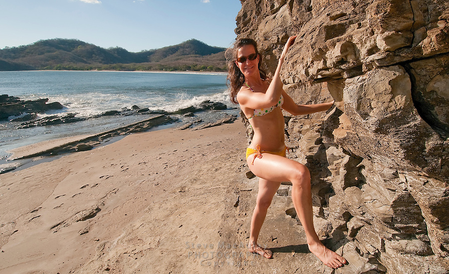 Young woman in yellow bikini walking and playing on private beach at Morgan's Rock Hacienda and Eco Lodge, Nicaragua