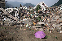 An umbrella lie in front of collapsed buildings in Beichuan, Sichuan, China on 15 May 2008. China now estimates the death toll to be around 50,000 as prospects of survival for those still buried diminishes.