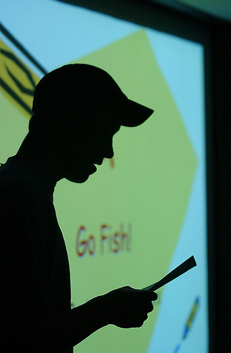 Matt Grevers reads the rules for his game, Go Fish, at Northwestern University.