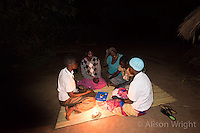 N. Uganda, Gulu District. Peter C. Alderman Foundation project. Alice Nora Kipwola, PCAF Trauma Counselor, assessing and counseling Christine Alum. Christine lost her arm during the war and struggles with depression. She has a son who helps her. Meeting at her house at night, they have no lights and live about an hour from the clinic. Chritine walks there for her monthly sessions.