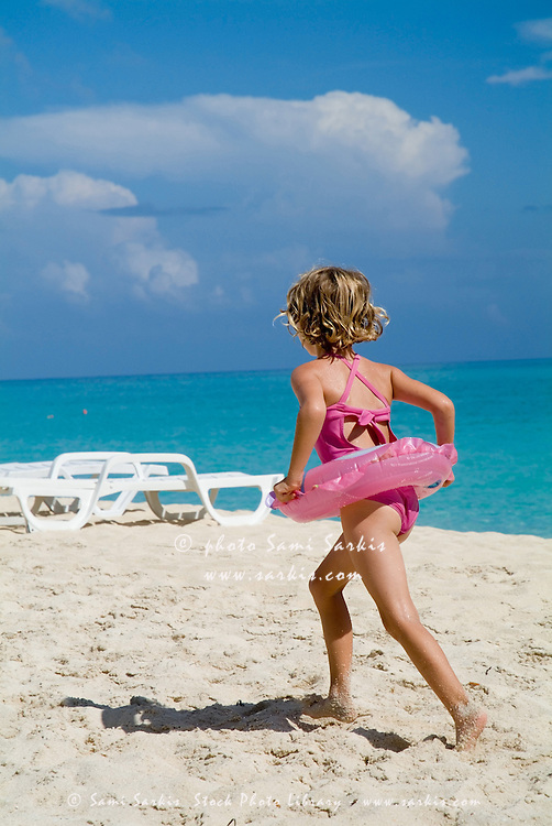 Little girl with an inflatable ring at the beach, Cayo Santa Maria, Cuba.