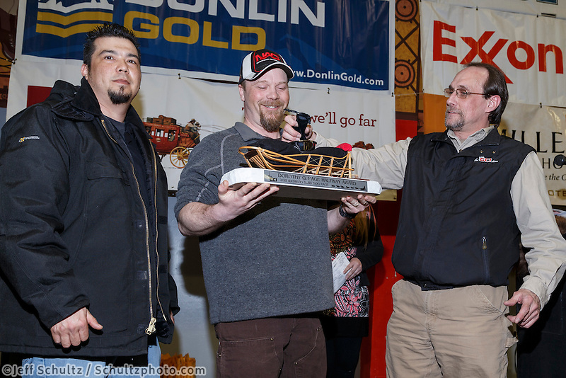Aaron Burmeister (center) recieves the GCI Dorothy G. Page Halfway award from Dave Fancott and Greg Menendez of GCI at the finishers banquet in Nome on Sunday  March 22, 2015 during Iditarod 2015.  <br /> <br /> (C) Jeff Schultz/SchultzPhoto.com - ALL RIGHTS RESERVED<br />  DUPLICATION  PROHIBITED  WITHOUT  PERMISSION