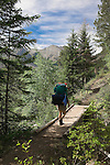 A backpacker walking across a footbridge in  the Bob Marshall Wilderness in Montana