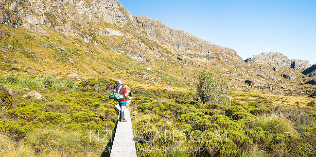 Young female tramper on Routeburn Track near Harris Saddle, Mt. Aspiring National Park, UNESCO World Heritage Area, Central Otago, New Zealand, NZ