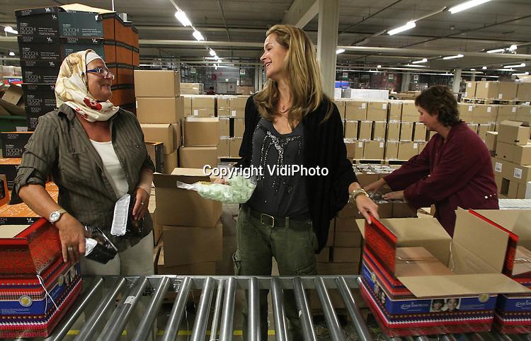 Foto: VidiPhoto..DUIVEN - Paulien Huizinga, ambassadeur van de Stichting Doe Een Wens heeft dinsdag bij de grootste inpakcentrale van Nederland, ICN/Makro Feestpakketten, meegeholpen met het inpakken van de eerste serie kerstpakketten met het logo van de stichting. Een deel van de opbrengst komt ten goede aan de stichting, die wensen vervult van kinderen met een levensbedreigende ziekte. Er worden ongeveer 40.000 pakketten klaargemaakt, die te koop zijn bij alle Nederlandse Makro-winkels. Een soortgelijke actie heeft vorig jaar ruim 93.000 euro opgebracht. De verkoop van de kerstpakketten start op 18 oktober..
