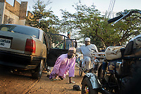 A member of KPVTA exits organizationís car at the KPVTA headquarters. Polio victims mostly can't walk and depending on how their limbs were affected by the disease they use different ways to move. Often they use knees and protect their hands with flip-flops.