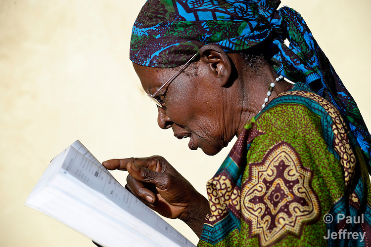 """Katherine Chimoteo, a woman in Riimenze, South Sudan, who says she is """"about 70"""", reads for the first time in years after finding some glasses that worked for her in a box of used glasses. She's reading aloud from """"Where Women Have No Doctor"""".."""