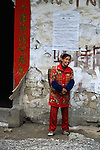 Young woman in red stands smiling near outside wall; gov't notice; small villages near Wuxi, China, Asia; rural China; 042403