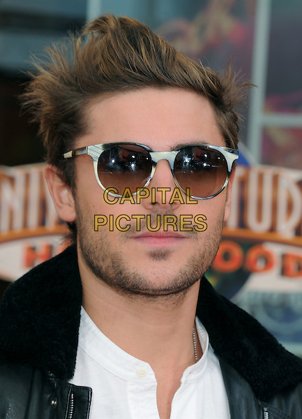 "Zac Efron.'Dr. Suess' ""The Lorax"" L.A. Premiere held at The Universal City Walk Theatre in Universal, Los Angeles, California, USA..February 19th, 2012 .headshot portrait white stubble facial hair black leather jacket sunglasses shades .CAP/RKE/DVS.©DVS/RockinExposures/Capital Pictures."