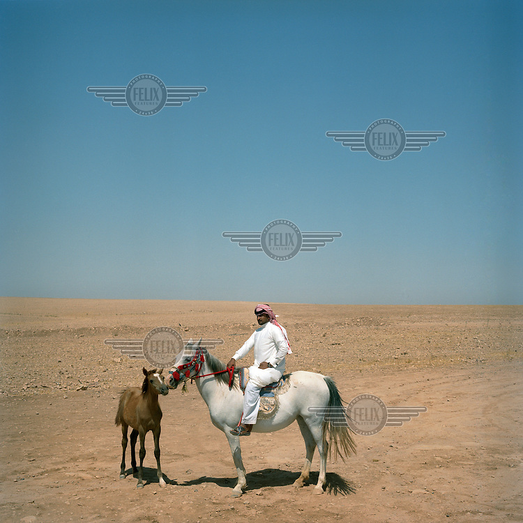 A Bedouin man poses for a portrait astride an Arab horse with its foal, in the desert near Naheat Al Jermeah, 80km West of Al Raaqa in North Eastern Syria.