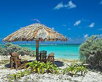 Anegada, British Virgin Islands, Caribbean<br /> Adirondack chairs under a palapa at Cow Wreck Bay