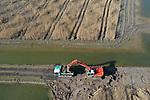 Foto: VidiPhoto<br /> <br /> BEMMEL – Met een graafmachine en een tweetal zogenoemde dumpers wordt dinsdag de laatste hand gelegd aan Park Lingezegen. Na het afgraven van de grondwallen tussen de kweekvijvers van moerasriet -naar verwachting vrijdag gereed- is de groene buffer tussen Arnhem en Nijmegen definitief klaar. De dijkjes worden door grondverzetbedrijf C. G. Van Leeuwen uit Bemmel verwijderd en het terrein geëgaliseerd. Aan het het 1700 (3400 voetbalvelden) grote natuur- en recreatiegebied is dan zes jaar gewerkt. Het deel dat nu afgegraven wordt ligt tegen kassengebied Next Garden (het voormalige Bergerden) aan en werd als eerste project van Lingezegen in aparte kweekvijvers ingeplant met moerasriet. Door het verwijderen van alle grondwallen ontstaat een enorm aaneengesloten moeras (Het Waterrijk) in de driehoek A325, Linge en Next Garden.