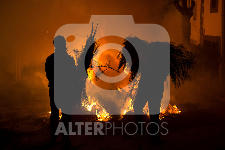 Two men add more wood to a bonfire during Las Luminarias celebration, as part of a ritual in honor of Saint Anthony the Abbot, the patron saint of domestic animals, in San Bartolome de Pinares, Spain. January 16, 2015. (ALTERPHOTOS/Victor Blanco)