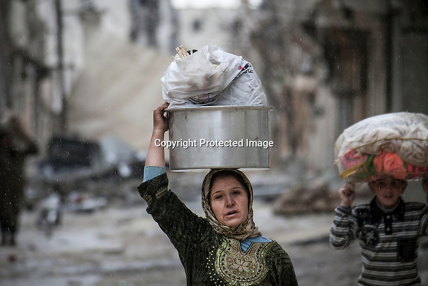 In this Tuesday, Dec. 11, 2012 photo, rain falls as a woman collects her belongings after her house was damaged due to fighting between Syrian rebels and government forces, while heavy artillery explosions are heard in the battlefield of Aleppo, Syria. (AP Photo/Narciso Contreras)