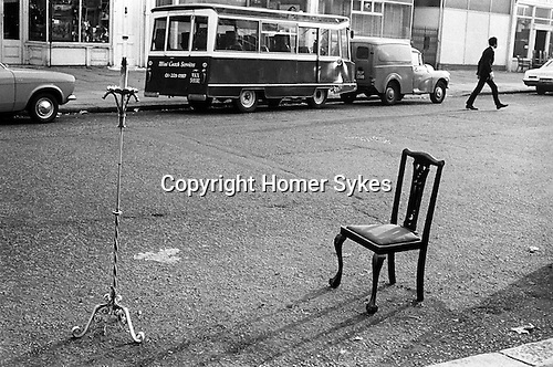 Saving a car parking space with household objects, a chair and lamp stand. No parking metres. Notting Hill West London 1970