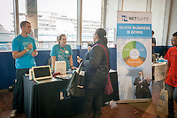 Netsuite employees speak with visitors at the TechDay New York event on Thursday, April 23, 2015. Thousands attended to seek jobs with the startups and to network with their peers. TechDay bills itself as the world's largest startup event with over 300 exhibitors. (© Richard B. Levine)