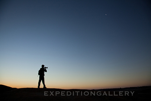 Silhouette of photographer at twilight in the Namib Desert, Dorob National Park, Namibia.