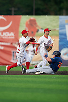 Auburn Doubledays shortstop Jose Sanchez (44) throws to first base as Jake Holton (29) slides in with second baseman Jake Alu (9) looking on during a NY-Penn League game against the Connecticut Tigers on July 12, 2019 at Falcon Park in Auburn, New York.  Auburn defeated Connecticut 7-5.  (Mike Janes/Four Seam Images)