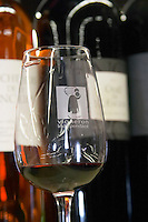 Glass embossed with Vigneron Independant, independent winegrower, and a symbol with a man carrying a cask. Domaine Enclos de la Croix. Languedoc. ISO standard shape wine tasting glass. France. Europe. Bottle.