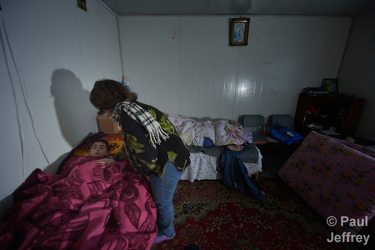 Roaa Sabah wakes her 10-year old son Behnam early in the morning in their home in Seje, Iraq. The community was flooded with displaced families when the Islamic State group took over nearby portions of the Nineveh Plains in 2014, including this family, which fled from Mosul to eventually live in a small, manufactured housing unit in Seje. Because Behnam and other displaced children came from communities with Arabic curriculum schools, they don't fit well in local schools that teach in Kurdish or Assyrian, so the Christian Aid Program Nohadra - Iraq (CAPNI) provides transportation for them to Duhok, where they study in schools that meet their needs.