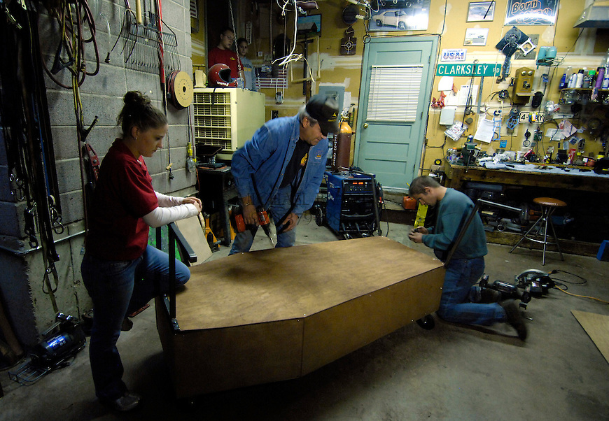 From the left, Mallory, John, and Jason Todd construct their coffin that will be run in the local Emma Crawford Coffin Race on Oct 27. The coffin will ultimately be decorated. Four racers will push the coffin containing Mallory Todd, dressed as Emma Crawford. Michael Brands for The New York Times.