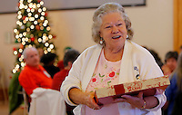 NWA Media/DAVID GOTTSCHALK - 12/9/14 - Rose Boitnott (cq) picks up the prize she one from playing a game of Bingo Tuesday December 9, 2014 during the Community Resources Division  8th annual Senior Giving Tree program and Holiday Party at the Fayetteville Senior Activity and Wellness Center. The Senior Giving Tree benefits seniors in the community by providing gifts for homebound seniors who participate in the Meals on Wheels program through the Fayetteville Senior Center.