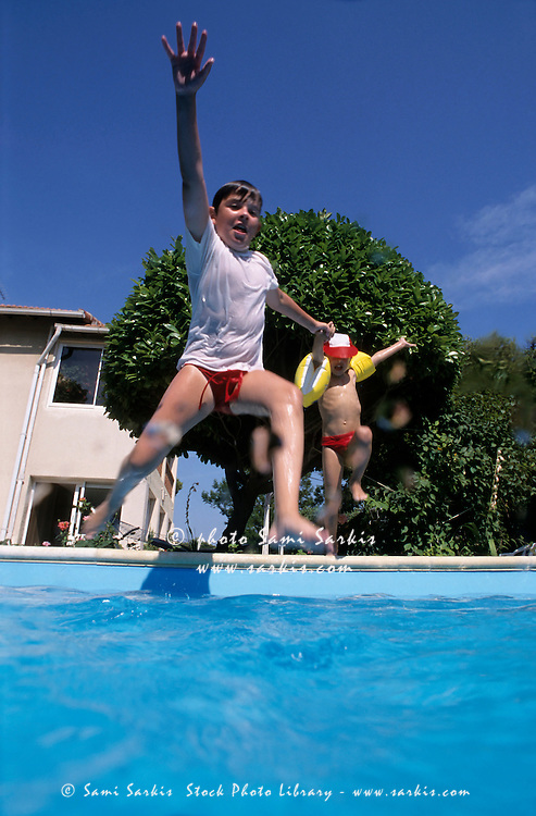 Boys jumping into a swimming pool, Marseille, France.