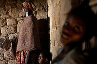 """Jawahir and her surviving children. She lost 3 children in   the war in Mogadishu..She is being assited by neigbors in State House IDP camp. They help her with food and rent for  the one room  house she lives in. The stone walls behind her are the original walls of  the State House building...In Jawahir's words:.""""I was born in Mogadishu.  ..I fled Mogadishu because of war.  I was there during the war, but then it came too close -I lost my husband.  ..I went first to Afgooye - I was there for one and a half months.  There's a very big problem because there is no water and very little food.  There's no help.  .We ran away to Afgooye - that's how we became safe.  ..Three of my children died, they were caught in the crossfire.  They were fleeing from fighting, but they got caught.  This happened just before we left.  .We came seeking peace and we found it.  We had only Hargeysa in our minds.  ..Inside Mogadishu, we used to run from one place to another to keep safe.  .We would move at dawn with the children walking from place to place.  .If you want to know how your friends are in Mogadishu, you go to a phone booth and call them.  It's impossibly dangerous to visit them.  ..After the Ethiopians left, things divided along tribal lines, they're fighting among themselves - the names they give themselves is just to hide the clan. ..So many innocent people are living in Mogadishu.  Every day a number of them die and they're not the ones fighting.  ..They go out to look for daily bread, they die.  ..Somebody must go out and look for food and water.  It's luck.  If they come back we eat.  .It's very sad when kids lose their parents. The parents go out sometimes and never come back. ..Days later the children leave the house to look for them and they get lost and maybe that's their end.  Every day, people are leaving but still there are people living in Mogadishu.  .I feel very bad because the war has touched me, it's touched my kids.  Now we are here - I don't know how I would"""