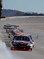 Nov. 1, 2009; Talladega, AL, USA; NASCAR Sprint Cup Series driver Denny Hamlin leads a pack of cars single file down the backstretch during the Amp Energy 500 at the Talladega Superspeedway. Mandatory Credit: Mark J. Rebilas-