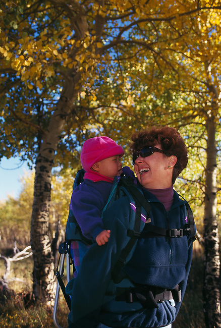 A mother and baby daughter enjoying the outdoors amidst fall color, Rocky Mtns, CO